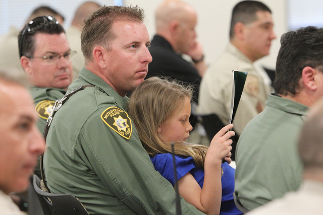 Jeff Harper holds his 7-year-old daughter Hailey Harper as she reads his award during Metro's commendation ceremony Wednesday, April 22, 2015. Harper was part of a group who was awarded a unit mer ...