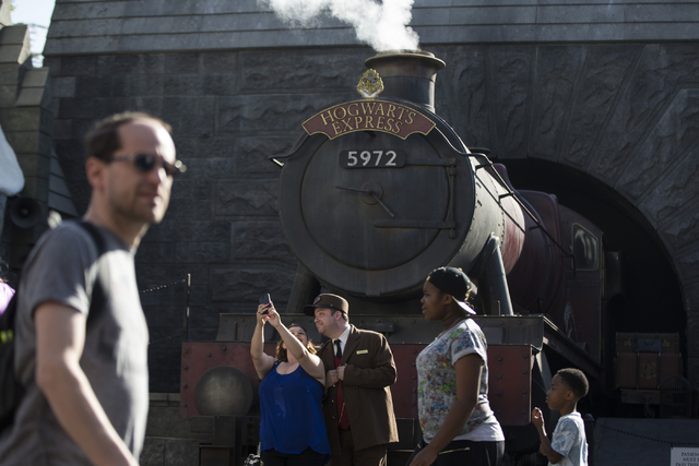 A woman poses for a photo in front of the Hogwarts Express with a conductor inside The Wizarding World of Harry Potter at Universal Studios on Friday, March 18, 2016, in Universal City, Calif. Eri ...