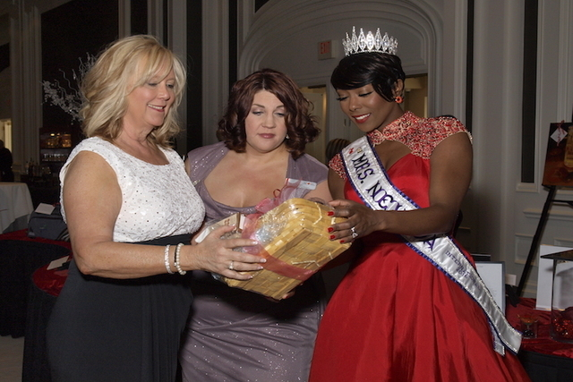 Debbie Smith, Jennifer Merback and Mrs. Aquillia Vang, reigning Mrs. Nevada International 2016, look at silent auction items during the Las Vegas Heart Ball at the Four Seasons Las Vegas Saturday, ...