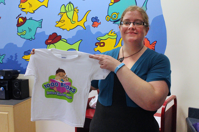 Kari Jensen, senior youth services specialist for Henderson Libraries, holds up a shirt promoting Henderson Libraries' 1,000 Books Before Kindergarten program. The idea of the program is to promot ...