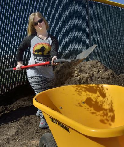 Student Tatiana Hass shovels dirt into a wheelbarrow at the community garden at Coronado High School in Henderson March 31. Bill Hughes/View