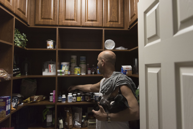 Holistic House Las Vegas founder Justin Hoffman shows herbal medication in the pantry at the house March 21. Jason Ogulnik/View