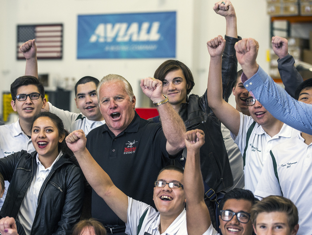 Greg Rochna, CEO of Maverick Aviation Group, center, poses for a photo with Rancho High School Aviation Academy students in the company's hangar at Henderson Executive Airport April 8. Jeff Scheid ...