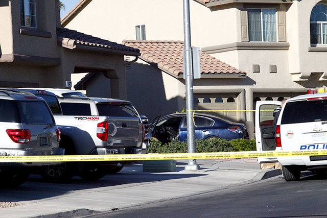 Henderson police investigate a shooting and vehicle crash involving the blue car, center, that left two men dead just after midnight Tuesday, April 12, 2016, at the corner of Trenier Drive and Rid ...