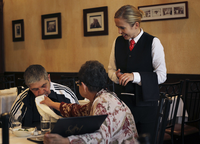 Nancy Vannucci, middle, wipes her husband Robert's mouth as server Bernadett Farkas looks on during dinner at Nora's Italian Cuisine in Las Vegas on Sept. 10, 2013. Robert, who is terminally ill,  ...