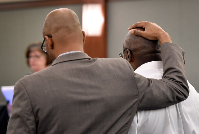 Defense attorney Jonathan MacArthur holds his hand on top of Billy Ray James as the clerk reads the verdict at the Regional Justice Center Tuesday, April 19, 2016, in Las Vegas. James was convicte ...