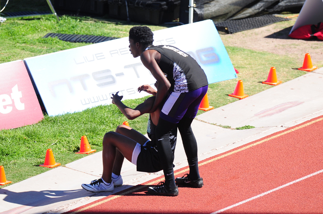 Sunrise Mountain runner Steven Walker, right, stops his race to help out Palo Verde runner Christian Jackson after Jackson fell while competing during the 400 meter dash in the Skyhawk Invitationa ...