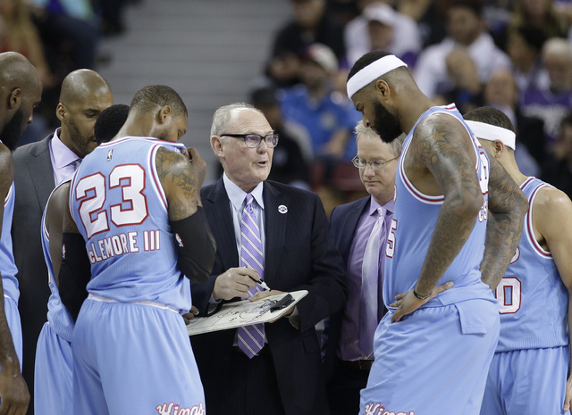 In this photo taken Saturday April 9, 2016, Sacramento Kings coach George Karl, center, huddles with team members Ben McLemore, left, and DeMarcus Cousins, right, during the second half of an NBA  ...