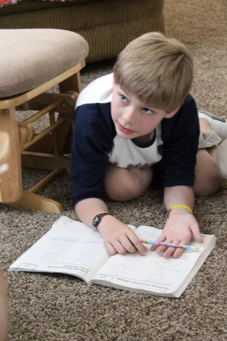 Larson Foster does homework in his Henderson home April 5. He and his family are trying to raise awareness about pediatric strokes after Larson suffered four within a year. Michael Lyle/View