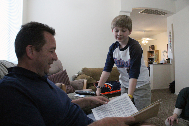Larson Foster, right, asks his dad, Larry, a question about homework April 5 in their Henderson home. The family continues to share its journey, raising awareness about pediatric strokes. Michael  ...