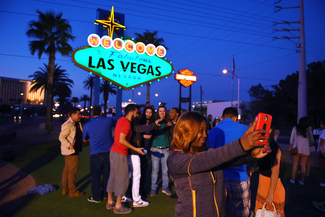 Tourists take photos as the Welcome to Fabulous Las Vegas sign on the Strip is colored green Tuesday, March 15, 2016. Southern Nevada's saw a 2.9 percent increase in visitors for March, the Las  ...