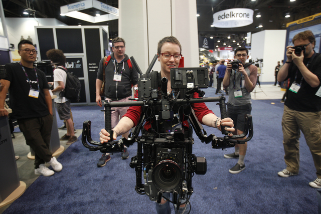 Scully tries on a Tilta 3-axis gimbal system with an Armor Man attachment in the showroom at the National Association of Broadcasters conference at the Las Vegas Convention Center Tuesday, April 1 ...