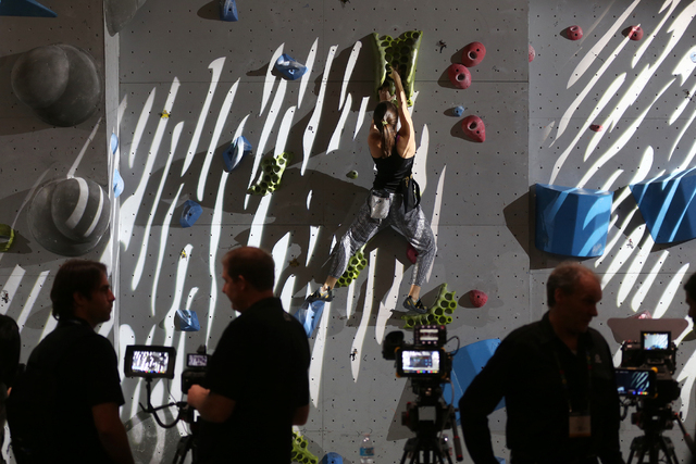 A climber climbs a wall as part of the display for Atomos touchscreens in the showroom at the National Association of Broadcasters conference at the Las Vegas Convention Center Tuesday, April 19,  ...