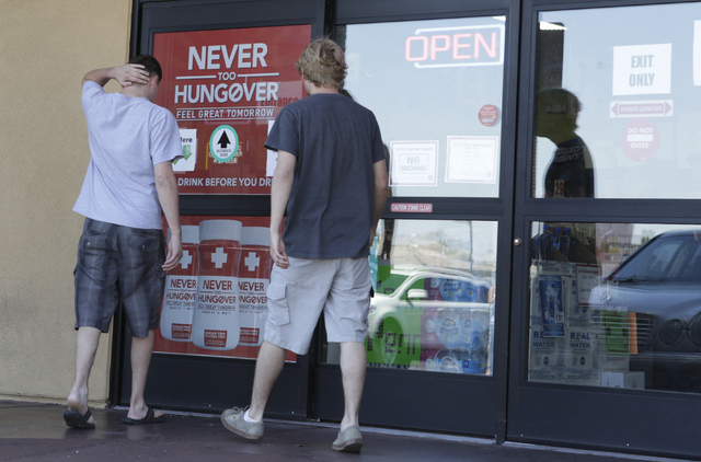 Dillon Chris, left, and his friend Blake Raw enter Leeճ Discount Liquor Wednesday, April 20, 2016. An employee was shot during a robbery Monday night at the liquor store at 8785 W. Warm Spri ...