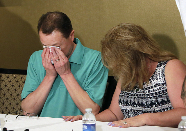 Lee's Discount Liquor robbery victim Matthew Christensen's father, Dennis weeps as his wife, Theresa looks down as they talk about the death of their son as they address the media at Excalibur hot ...