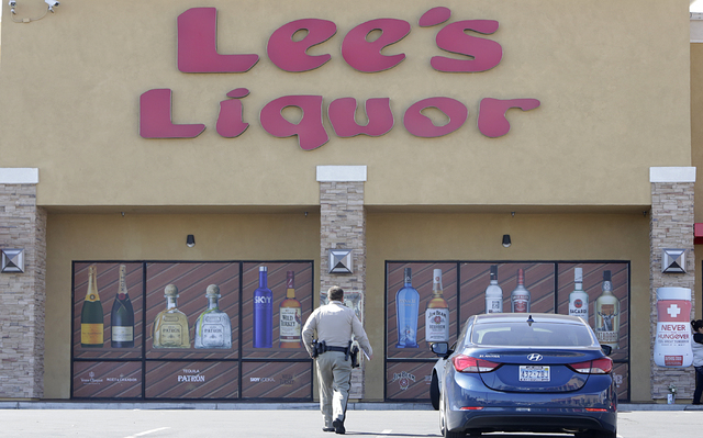 A Metro police officer investigates on Tuesday, April 19, 2016, after a Lee's Discount Liquor employee died after being shot during a robbery Monday night at the store, 8785 W. Warm Springs Road.  ...