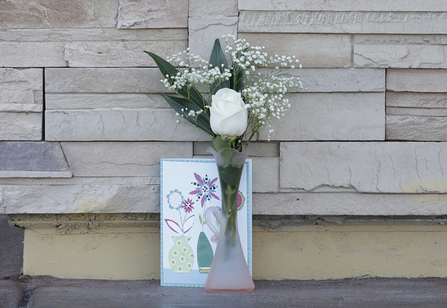 A rose and card are placed outside Lee's Discount Liquor, 8785 W. Warm Springs Road, Tuesday, April 19, 2016. A store employee died after being shot during a robbery Monday night at the store. (Bi ...