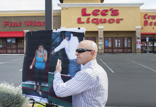 Metro officer Larry Hadfield points at photos of the suspects in a fatal shooting that took place Monday night at Lee's Discount Liquor at 8785 West Warm Springs Road, Tuesday, April 19, 2016, in  ...