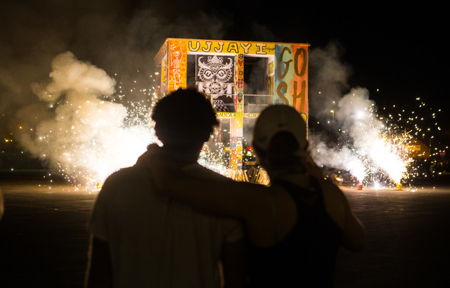 Artist Scott Cohen, creator of the Life Cube Project, left, with daughter Natasha, watches as the fire ceremony goes on for the Life Cube in downtown Las Vegas on Saturday, April 2, 2016. (Chase S ...