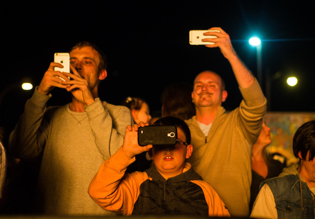 People watch and record as the fire ceremony goes on for the Life Cube in downtown Las Vegas on Saturday, April 2, 2016. (Chase Stevens/Las Vegas Review-Journal) Follow @csstevensphoto