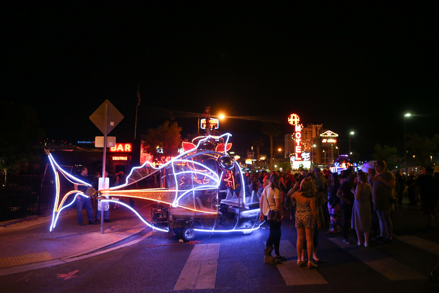 People stand near a decorated vehicle following the Life Cube fire ceremony in downtown Las Vegas on Saturday, April 2, 2016.(Chase Stevens/Las Vegas Review-Journal)  Follow @csstevensphoto