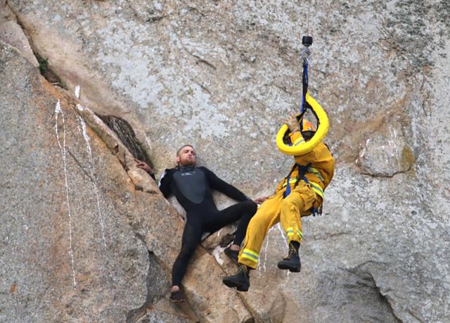 Michael Banks is stranded on a ledge some 80 feet off the ground on Morro Rock, a landmark in Morro Bay, Calif., Thursday, April 7, 2016. (Bob Isenberg/The Associated Press)