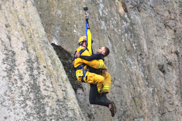 Michael Banks is rescued after being stranded on a ledge some 80 off the ground on Morro Rock, a landmark in Morro Bay, Calif., Thursday, April 7, 2016. (Bob Isenberg/The Associated Press)