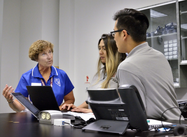Debbie Letts, a volunteer with the Nevada State Health Insurance Assistance Program, left, works with pharmacy students Joann Lagman, center, and Glen Lee in the Medicare Call Lab at Roseman Unive ...