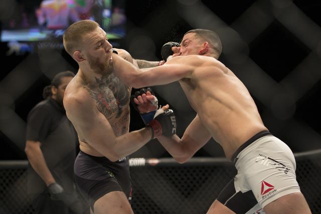 Conor McGregor, left, battles against Nate Diaz in their men's welterweight title bout during UFC 196 at MGM Grand Garden Arena on Saturday, March 5, 2015 in Las Vegas.  (Erik Verduzco/Las Vegas R ...