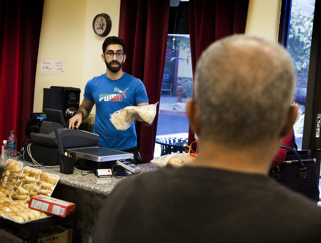 Haidar Karouni, talks to a costumer while working at the his family's Afandi Restaurant, 5181 W. Charleston Blvd. on Friday, Nov. 13, 2015. Karouni is waiting for is U.S. citizenship to be approve ...
