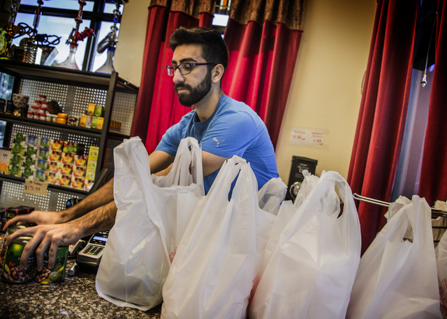 Haidar Karouni, checks out groceries while working at the his family's Afandi Restaurant, 5181 W. Charleston Blvd. on Friday, Nov. 13, 2015. Karouni is waiting for is U.S. citizenship to be approv ...
