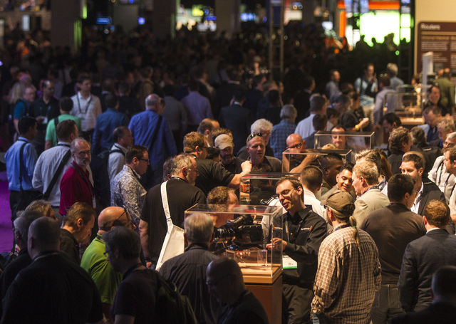 People mingle around the Blackmagic booth in the South Hall at the Las Vegas Convention Center, 3150 Paradise Road during National Association of Broadcasters Show on Monday, April 13, 2015. Aroun ...