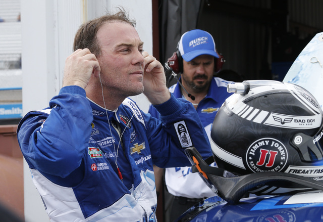 Kevin Harvick takes his earplugs out as he arrives in the garage after practice for Sunday's NASCAR Sprint Cup auto race at Richmond International Raceway in Richmond, Va., Saturday, April 23, 201 ...