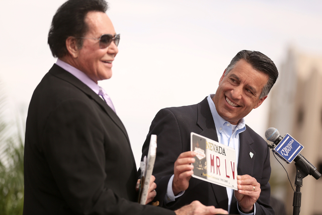 Nevada Gov. Brian Sandoval gives entertainer Wayne Newton a vanity plate during the Project Neon groundbreaking in Las Vegas on Thursday, April 7, 2016.  The $1.5 billion project will add traffic  ...