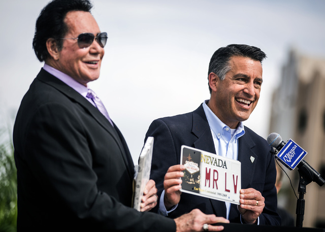 Nevada Gov. Brian Sandoval, right, presents a license plate to entertainer Wayne Newton during the groundbreaking for Project Neon near The Smith Center for the Performing Arts in Las Vegas on Thu ...