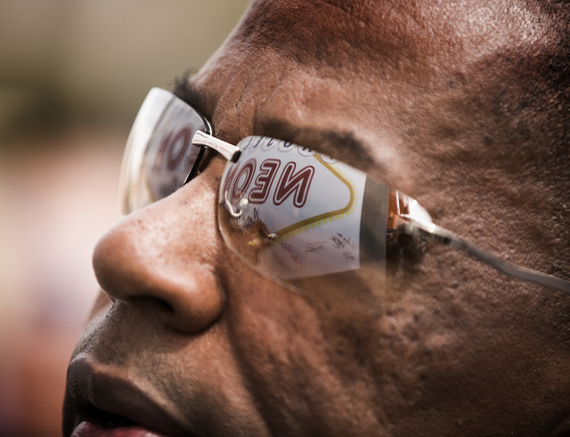 A reflection of a Project Neon sign is seen in the glasses of Clark County Commissioner Lawrence Weekly during the groundbreaking for Project Neon near The Smith Center for the Performing Arts in  ...