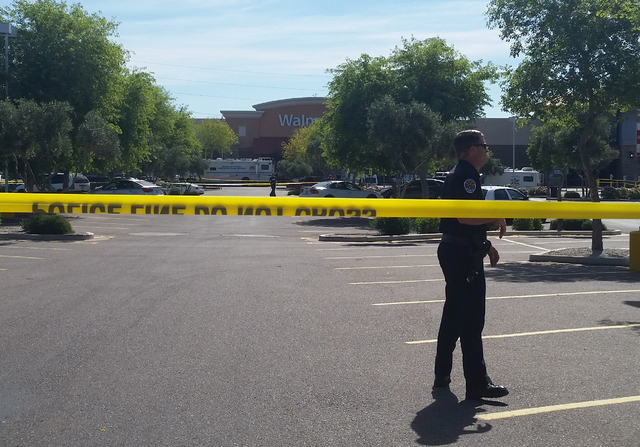 Chandler police spokesman Seth Tyler stands behind crime tape at the scene of a police involved shooting at a Walmart store on Saturday, April 23, 2016 in Chandler, Ariz.  (Terry Tang/The Associat ...