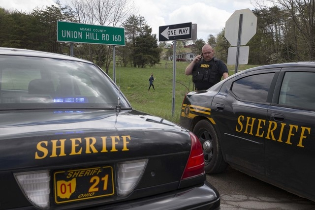 Authorities create a perimeter near a crime scene on Union Hill Rd, Friday, April 22, 2016, in Pike County, Ohio. Shootings with multiple fatalities were reported along a road in rural Ohio. (AP P ...