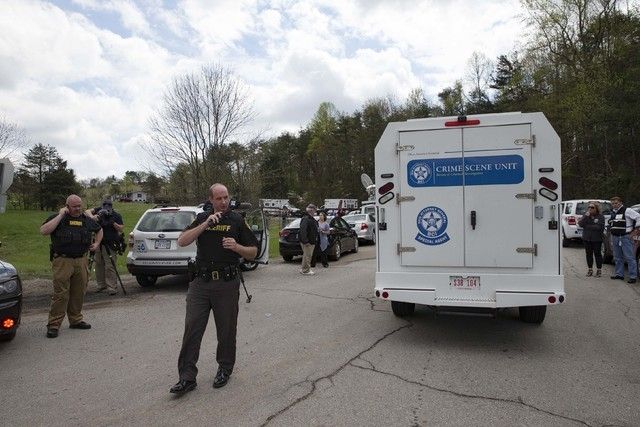 Authorities allow crime scene investigation vehicles to pass a perimeter checkpoint, Friday, April 22, 2016, in Pike County, Ohio. Shootings with multiple fatalities were reported along a road in  ...