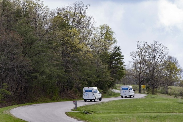 Crime scene investigation vehicles drive up Union Hill Road as they approach the location of a reported multiple shooting, Friday, April 22, 2016, in Pike County, Ohio. (AP Photo/John Minchillo)