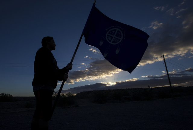 Kota Lavalle holds the Shivwits Band of Paiutes flag before the start of the Gold Butte Culture Walk, Saturday, April 23, 2016, in Gold Butte, Nevada. The fourth annual event is aimed at promoting ...