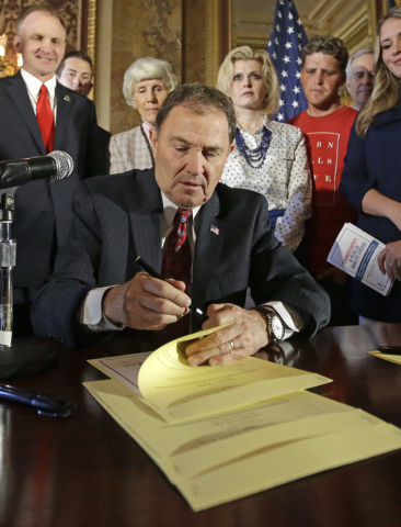 Utah Gov. Gary Herbert, center, uses his pen during a ceremonial signing of a state resolution declaring pornography a public health crisis Tuesday, April 19, 2016, in Salt Lake City. Herbert reco ...