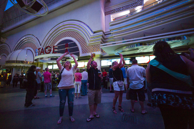 People watch as a tribute to Prince, who passed away at age 57, is shown at Fremont Street Experience in Las Vegas on Thursday, April 21, 2016. (Chase Stevens/Las Vegas Review-Journal) Follow @css ...