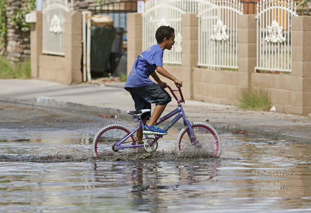 A child rides a bike through a flooded area of Valley View Boulevard near San Angelo Avenue Saturday, April 9, 2016, in Las Vegas. (Ronda Churchill/Las Vegas Review-Journal)