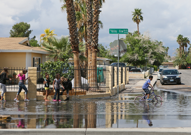 Children make their way through and play along a flooded area of Valley View Boulevard near San Angelo Avenue Saturday, April 9, 2016, in Las Vegas. (Ronda Churchill/Las Vegas Review-Journal)