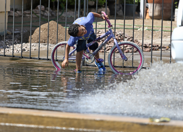 A child waits to be splashed by cars driving along a flooded area of Valley View Boulevard near San Angelo Avenue Saturday, April 9, 2016, in Las Vegas. (Ronda Churchill/Las Vegas Review-Journal)