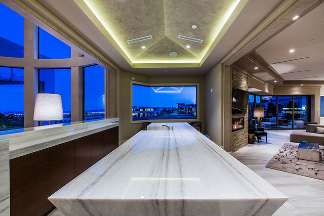 A large white bar sits between the living room and the gourmet kitchen and great room. (Courtesy Shapiro & Sher Group)
