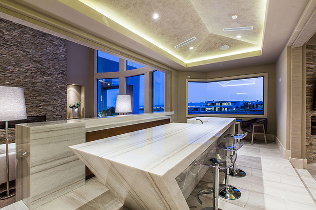 A large white bar  between the living room and the gourmet kitchen and great room is an artistic component to the home. (Courtesy Shapiro & Sher Group)