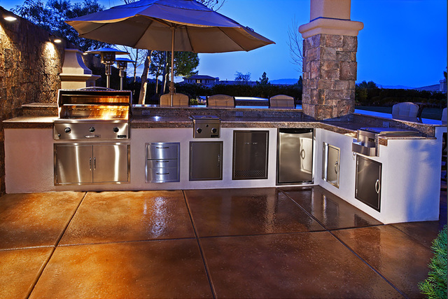 Outdoor kitchens can range in complexity from a grill and some counter space to three to four grills, side burners, sinks, built-in pizza ovens, a refrigerator and storage drawers.  (COURTESY OF L ...