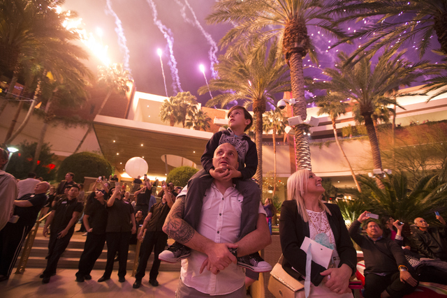 Giuseppe Acquisto, with his 9-year-old son Flavio on his shoulders, and his wife Patrizia, watch the fireworks show during the Red Rock Resort 10th birthday celebration at Red Rock casino-hotel on ...
